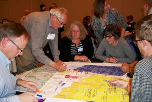 "UP""s allie Rick (right and Clodagh B asgtian (standing, center) watch as Cameron Park resident George Chapman makes notes on the map during a table-top exercise."